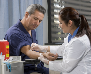 Healthcare provider taking blood sample from man's arm.