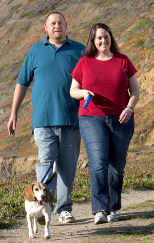 Man and woman outdoors walking a dog.