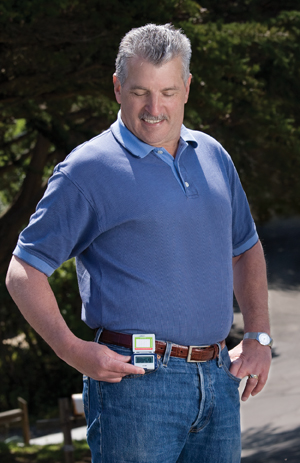 Man outside looking at pedometer on his belt.
