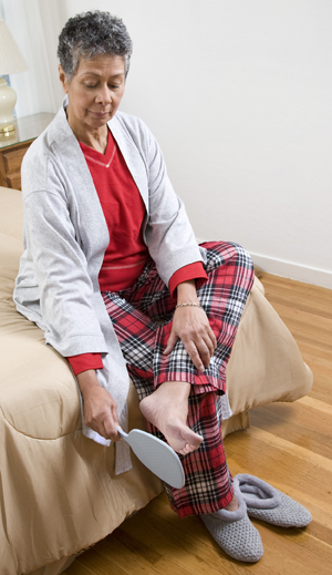 Woman sitting on edge of bed looking at sole of foot with mirror.