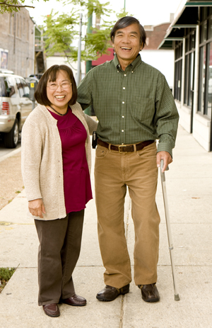 Man with cane walking on city street with woman.