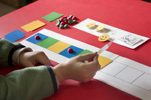 Child placing colored squares in sequence on table.