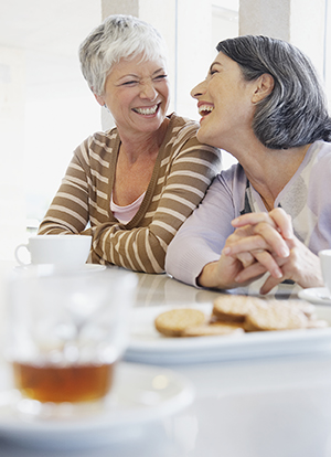 Two women friends talking, having coffee and dessert.