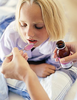 Close up of hands giving liquid medicine to girl lying in bed.