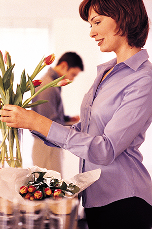 Woman placing flowers in vase with husband in the background.