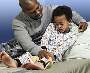 Father massaging young son's leg because of growing pains.