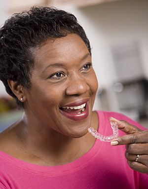 Woman placing an Invisalign clear aligner in her mouth.