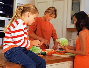 Young family making salad in kitchen.