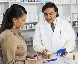 Woman talking to pharmacist at pharmacy counter.