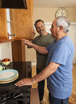 Older man standing in front of an open cupboard and pointing at it. A younger man stands next to him watching.