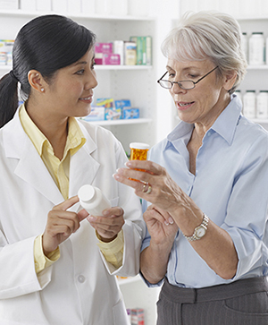 Pharmacist talking to woman about pills.