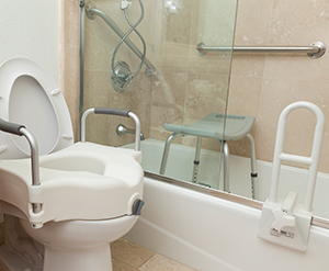 Toilet with modified seat, shower chair, grab bar and handheld water nozzle in bathroom.