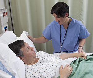 Healthcare provider checking on man in hospital bed.