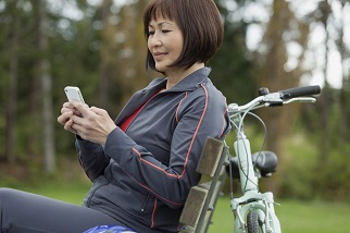 Woman on park bench look at phone