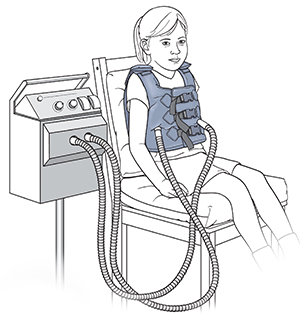 Girl sitting in chair wearing vibrating vest.