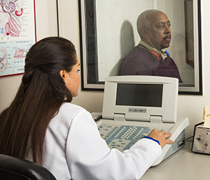 Audiologist performing hearing test on man sitting in booth.