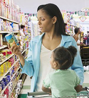 Woman in grocery store with baby, reading nutrition label on can.