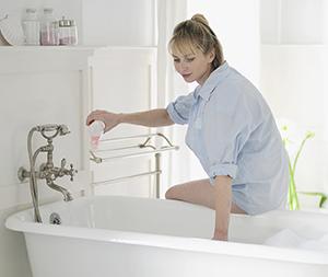 Woman running bath water.