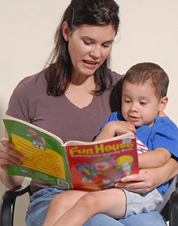Woman holding preschool boy in lap, reading.