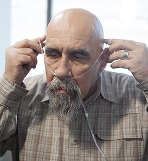Man putting on a nasal cannula.