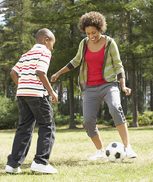 Woman and boy playing soccer in park.