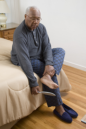 Man inspecting sole of foot with mirror.