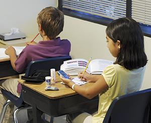 Girl checking blood sugar at school.