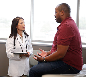 Man in exam room talking to doctor.