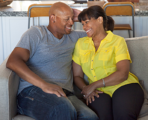 Man and woman sitting together on couch, smiling.