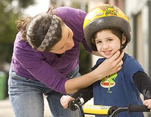 Woman putting helmet on preschooler boy on bike.