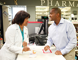 Pharmacist talking to man at pharmacy counter.