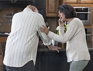 Man grabbing his head in pain in the kitchen. Woman calling for help on telephone.