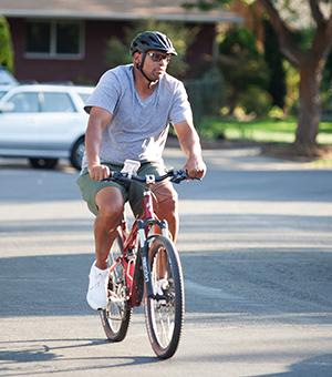 Man bicycling on neighborhood street.