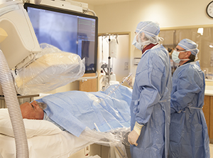 Two technicians performing angiography on male patient.