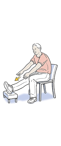 Man sitting with foot on stool doing leg stretch exercise.