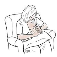 Woman breastfeeding premature baby in cross-cradle hold.