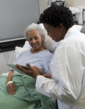 Healthcare provider with electronic tablet talking to woman in hospital bed.