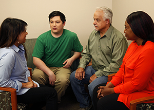 Group of two men and two women talking together.