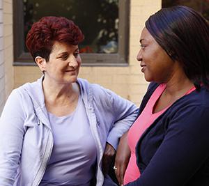 Two women talking outdoors.