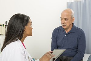 Man talking with health care provider in exam room.