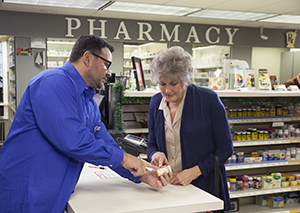 Pharmacist showing woman bottle of pills at pharmacy counter.