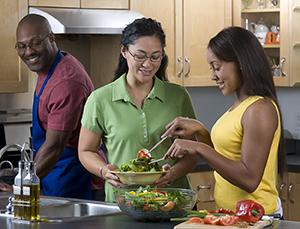 Family in kitchen preparing salad.