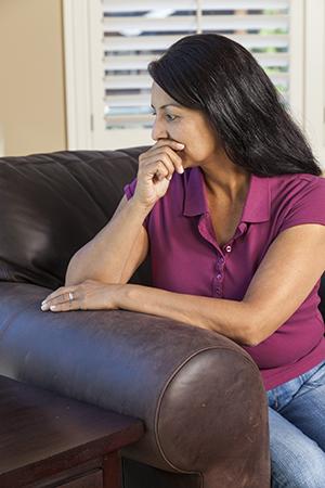Woman sitting on chair looking sad.