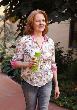 Woman with water bottle walking outdoors.