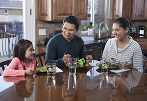 Man, woman, and girl eating healthy food at home.