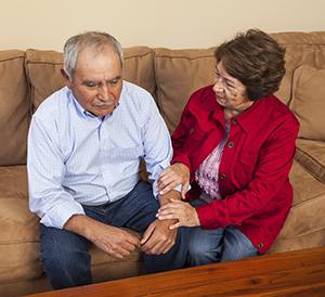 Senior female comforting senior male.