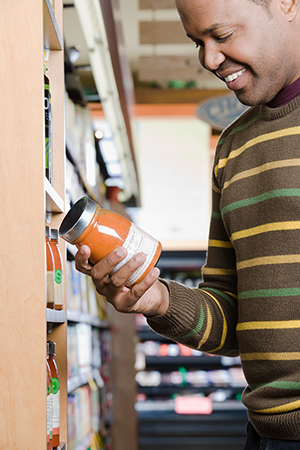 Man reading food label on can in grocery store.