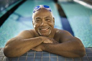 Man in swimming pool, smiling.