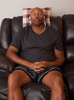 Man with headphones on relaxing in chair.