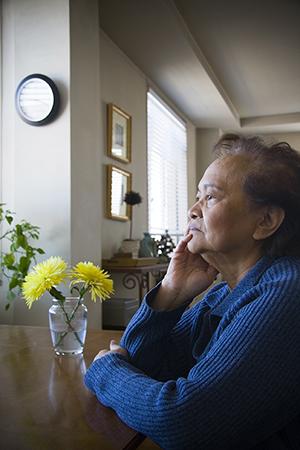 Woman sitting at table, looking sad.